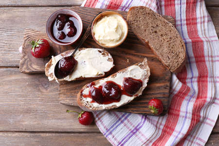 Fresh toast with homemade butter and strawberry jam on wooden background
