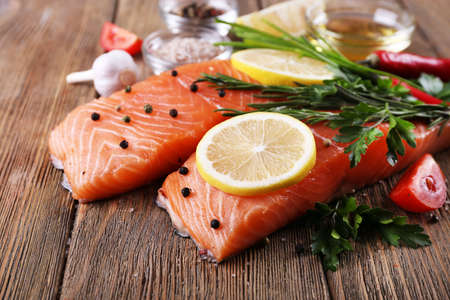 Photo for Fresh salmon with spices and lemon on wooden table - Royalty Free Image
