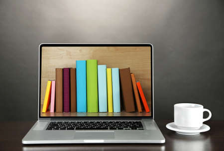 E-learning concept.  Digital library - books inside laptop