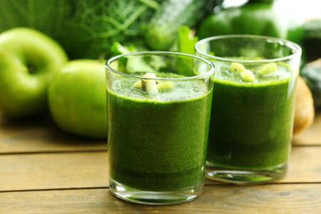 Green fresh healthy juice with fruits and vegetables on wooden table backgroundの写真素材