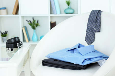 Men's clothes on chair with shelf on background
