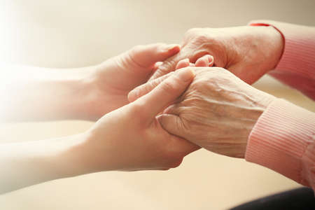 Photo pour Old and young holding hands on light background, closeup - image libre de droit