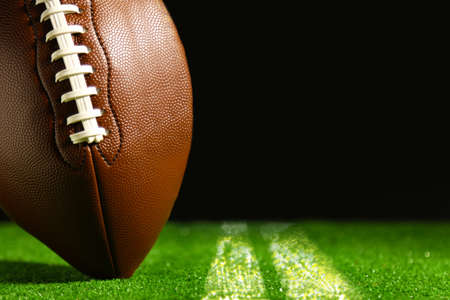 American football on green grass on black background