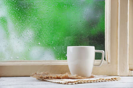 Cup of hot drink with napkin on windowsill on rain backgroundの写真素材