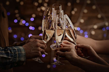 Photo pour Clinking glasses of champagne in hands on bright lights background - image libre de droit
