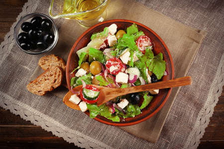 Bowl of Greek salad served on napkin on wooden background closeup