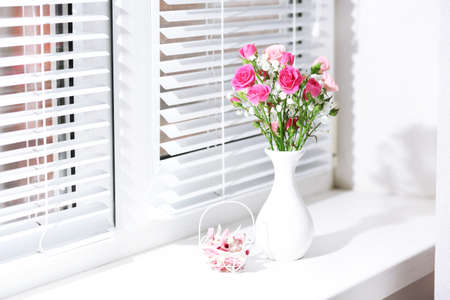 Photo pour Bouquet of pink roses in white vase on windowsill background - image libre de droit