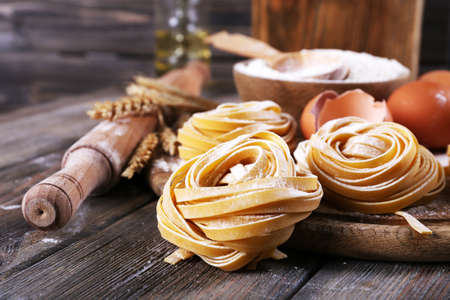 Raw homemade pasta and ingredients for pasta on wooden