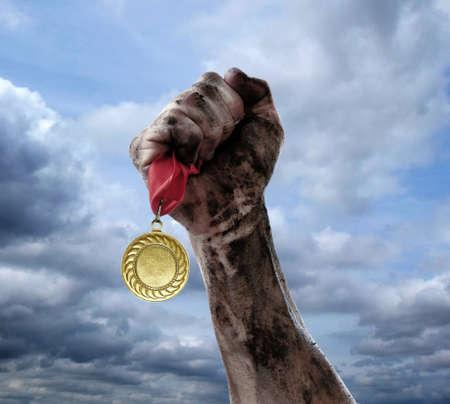 Golden medal in hand on sky background