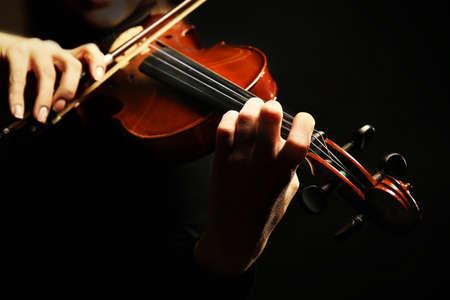 Photo pour Violinist playing violin on dark background - image libre de droit
