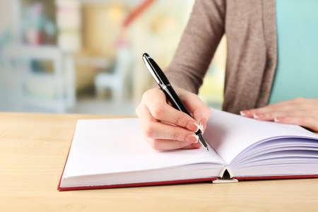 Photo pour Female hand with pen writing on notebook, closeup - image libre de droit