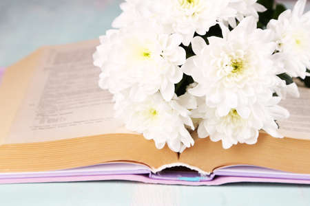 Bouquet of flowers with book on color wooden table, closeup