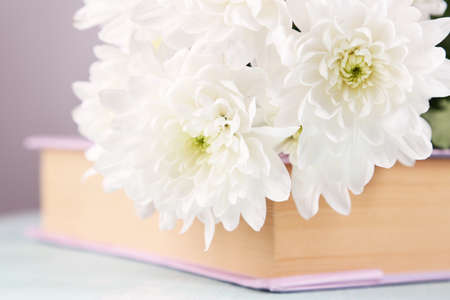 Bouquet of flowers with book on light background, closeup