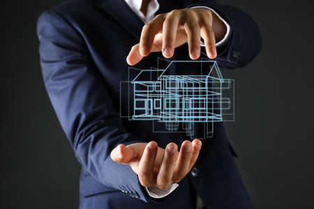 Real estate offer. Businessman holds an artificial model of the house