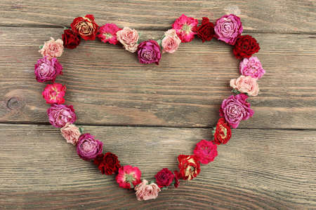 Dried flowers in shape of heart on wooden background