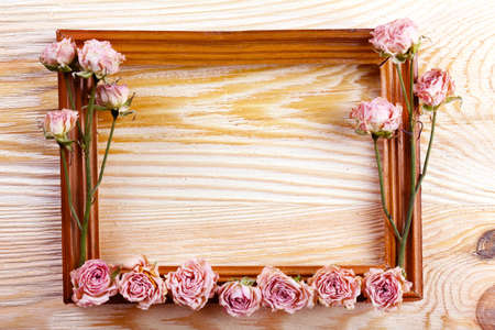 Photo frame with dried flowers on wooden background