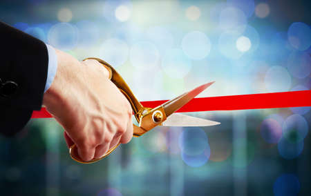Photo pour Businessman cutting red ribbon with pair of scissors close up - image libre de droit