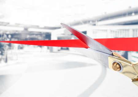Scissors cutting red ribbon close up