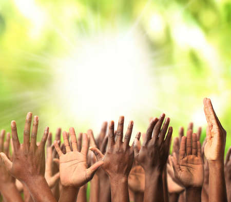 Crowd raising hands on green blurred nature background