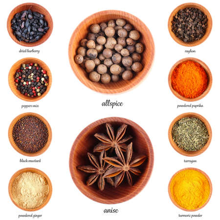 Large collection of different spices and herbs in wooden bowls, isolated on white background