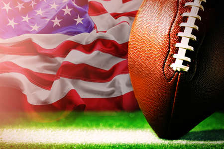 American football on green grass, on flag of United States of America background