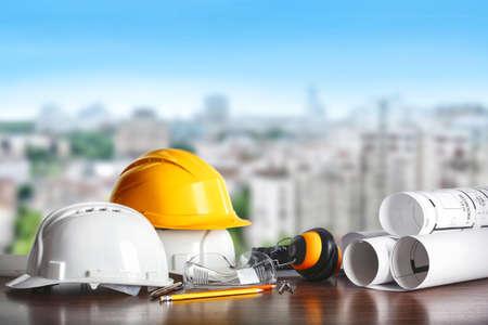Photo pour Construction concept. Architect equipment: helmets, blueprint and pencil on the table and view of city - image libre de droit
