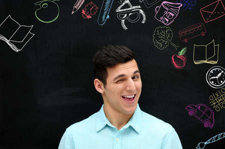 Young man on blackboard background. Creative sketches on chalkboard. Children development concept.