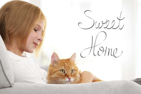 Cute girl with cat on sofa. Text SWEET HOME.