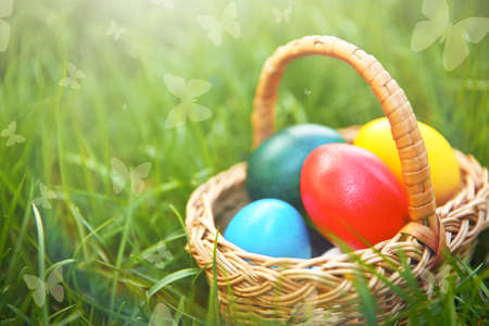 Wicker basket with Easter eggs on green grass