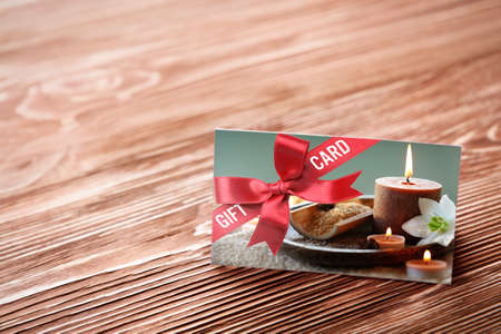 Foto de Holiday celebration concept. Spa service gift card on wooden background - Imagen libre de derechos