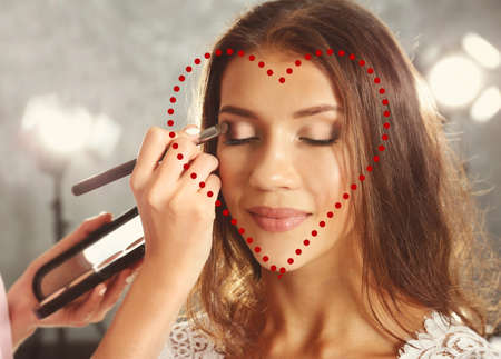 Professional makeup artist applying eyeshadow. Heart shaped face concept