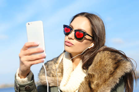 Young beautiful woman in sunglasses with hearts taking selfie outdoor