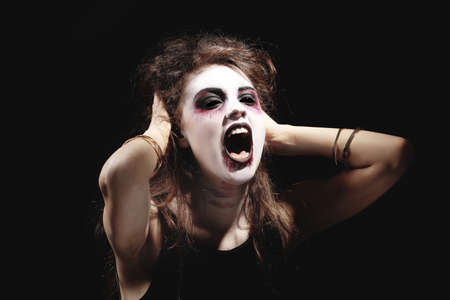 Young woman in color contact lenses, with Halloween makeup on black background