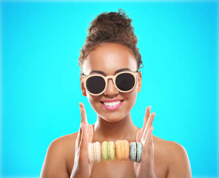 Young African-American woman holding macaroons on color background