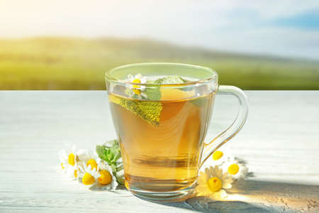 Hot chamomile tea in cup with flowers on wooden table outdoor