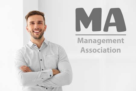 Concept of management association. Young businessman on light background
