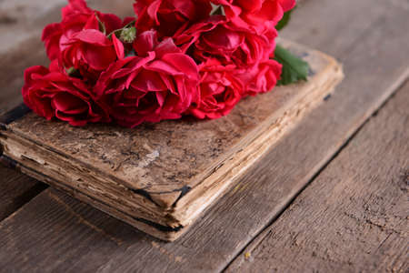 Old book with beautiful roses on wooden table close up