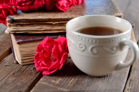 Old books with beautiful flowers and cup of tea on wooden table close up