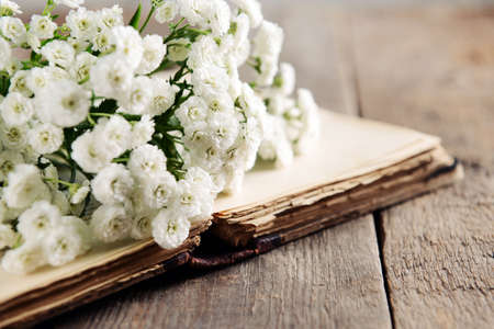 Old book with beautiful flowers on wooden table close up