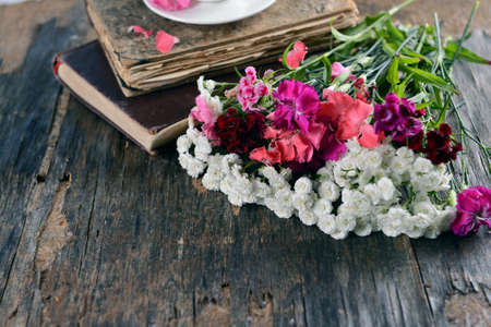 Old books with beautiful flowers on wooden table close up
