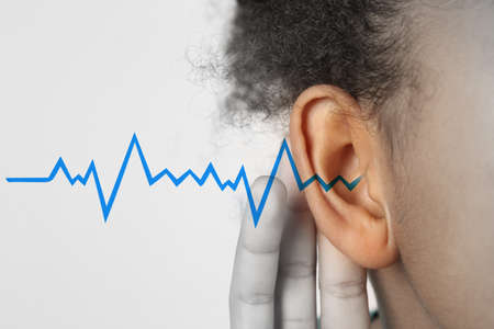 Photo pour African-American girl with symptom of hearing loss on light background - image libre de droit