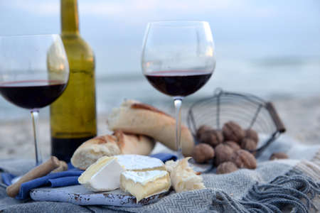 Beautiful romantic composition of red wine, bread and nuts on sandy beach