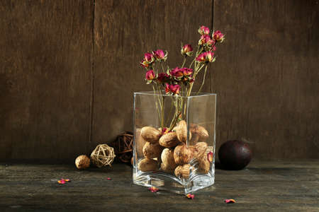 Composition of nuts, wooden balls and stale flowers in glass on wooden background