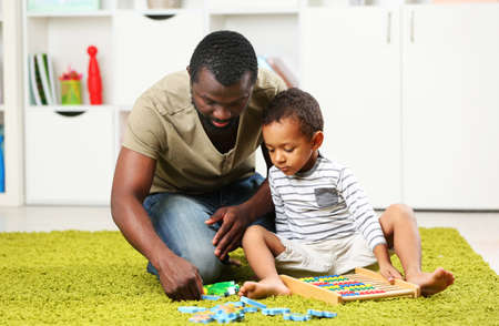 Photo pour Father and son playing in the children room - image libre de droit