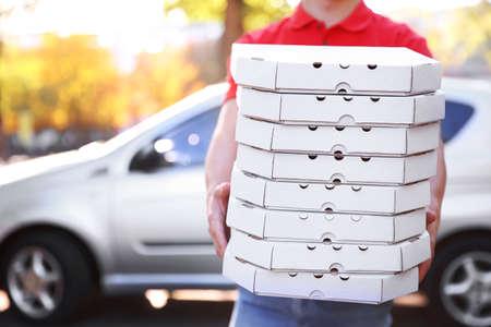 Photo pour Pizza delivery boy holding boxes with pizza near car - image libre de droit