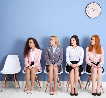 Young businesswomen sitting on a chair and looking right in blue hall