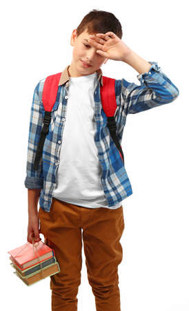 Tired little boy with red backpack and bunch of books, isolated on white