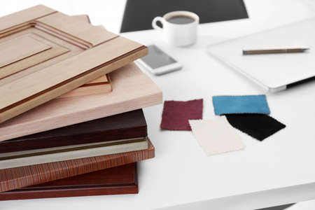 Samples of wooden panels, pieces of cloth for furniture and door on white table