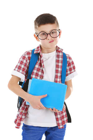Confused little boy with glasses and back pack holding books, isolated on white