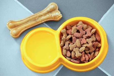 Pet food in a yellow bowl on a floor.